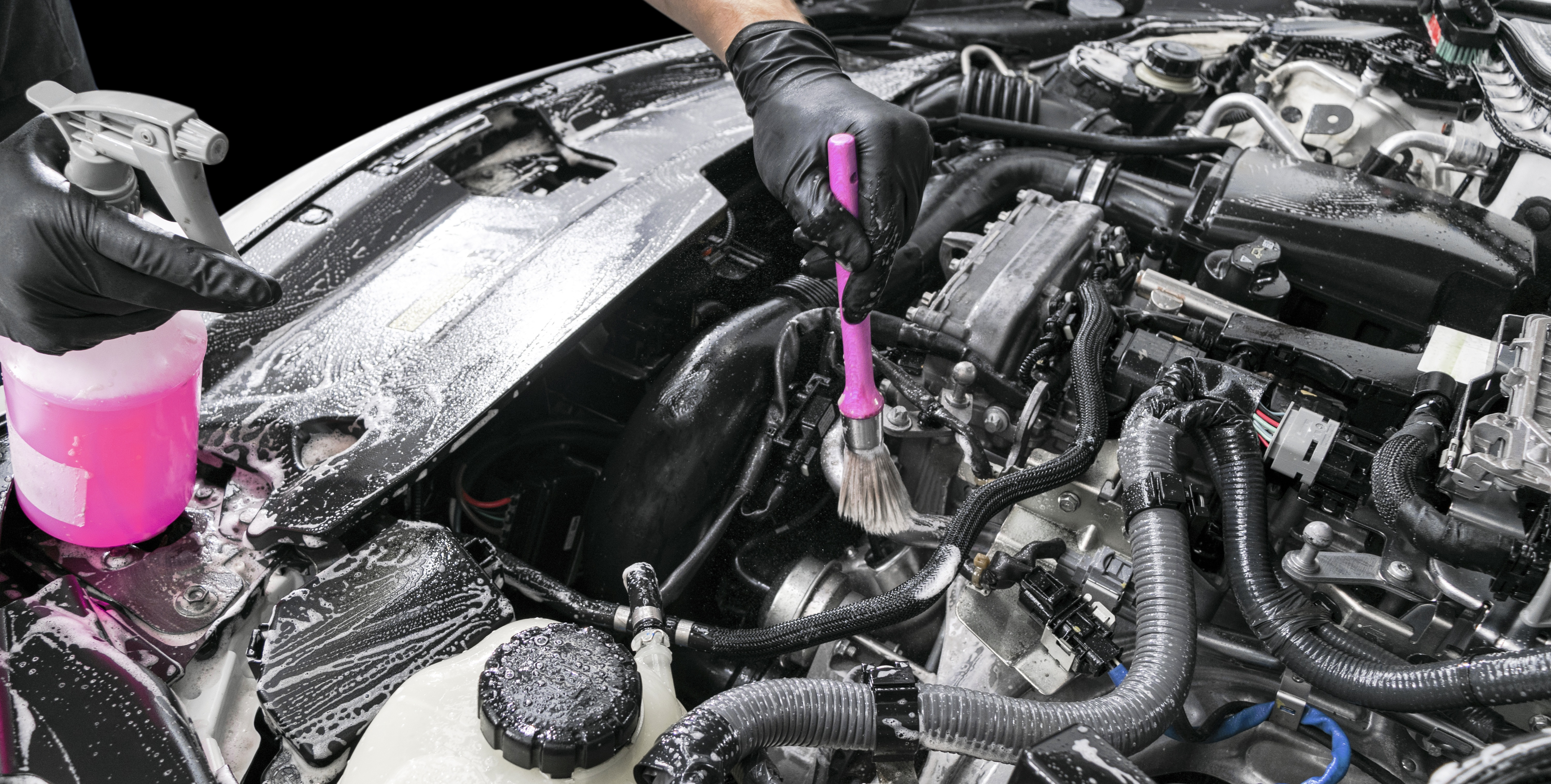 A man cleaning car engine with shampoo and brush. Car detailing or valeting concept. Selective focus. Car detailing. Cleaning with sponge. Worker cleaning. Car wash concept solution to clean. Isolated